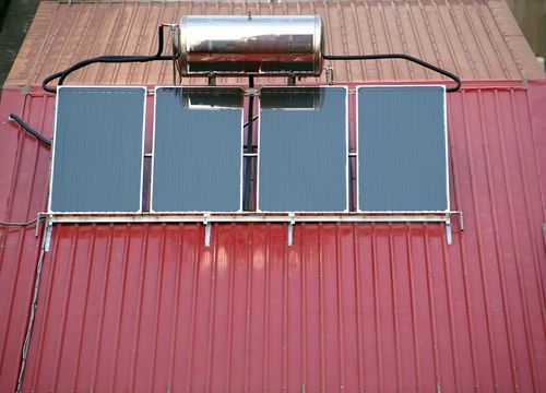 Solar water heating system mounted on a corrugated metal roof