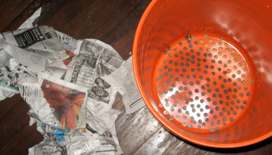bucket with holes drilled in it and newspaper scraps