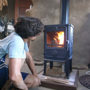 man sitting next to small wood stove