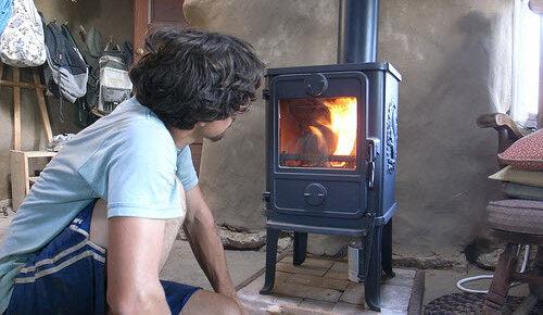 man sitting next to small wood stove