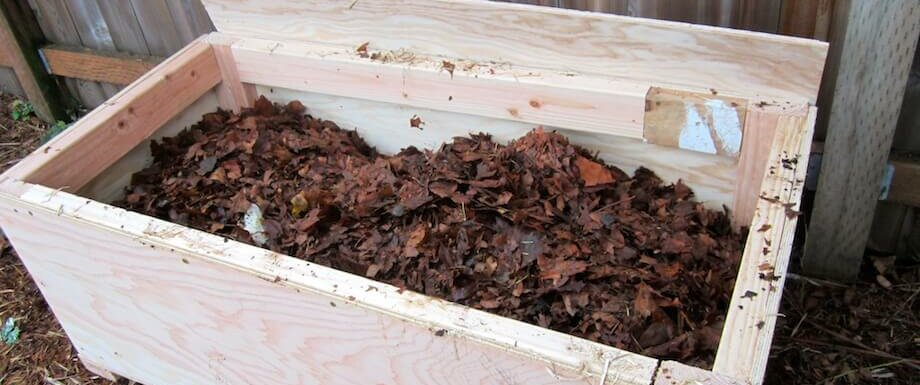 worm bin filled with a dirt, then a layer of leaves