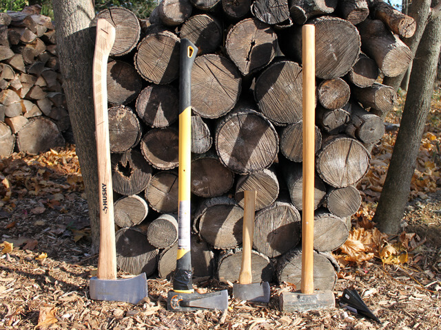 tools for chopping wood leaning against a stack of wood