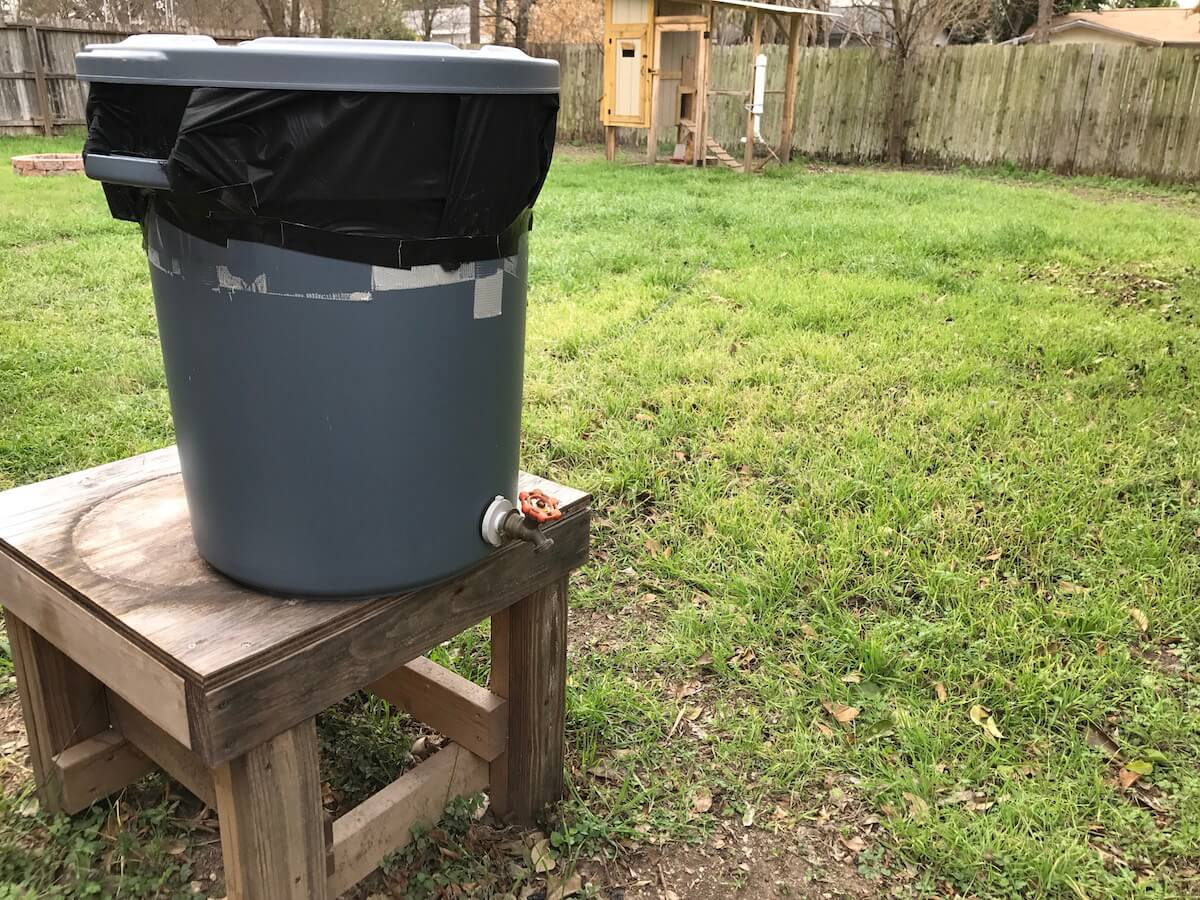 a rain barrel in a backyard