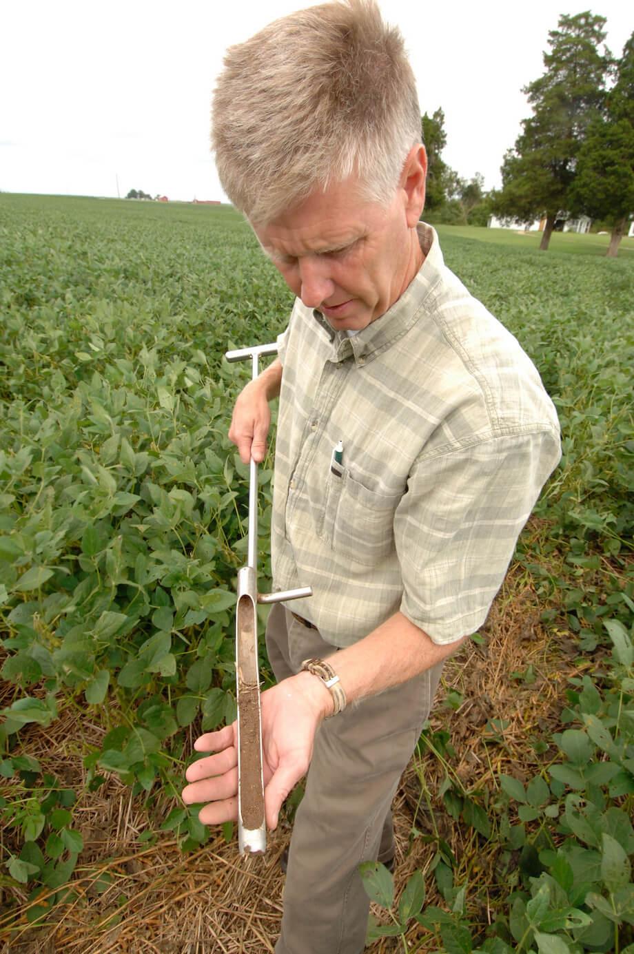 crop consultant draws soil sample