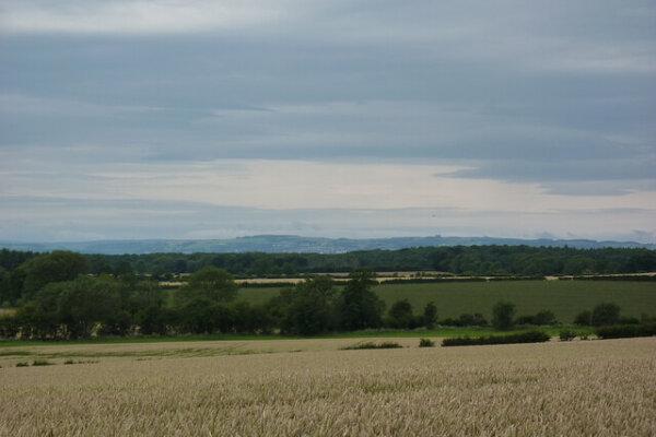Fields of dry grass spread across rolling hills, a few trees line the horizon.