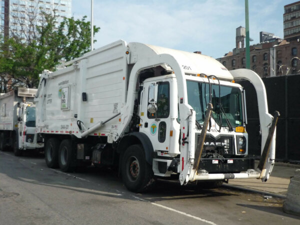 The garbage truck is stopped by the edge of a curb.
