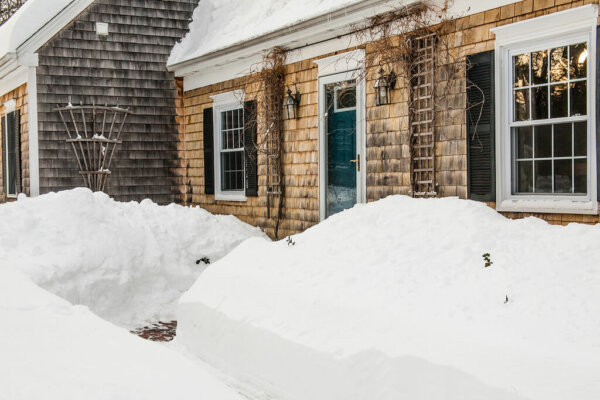 piles of snow outside of a home