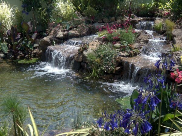 man made backyard water feature with two waterfalls