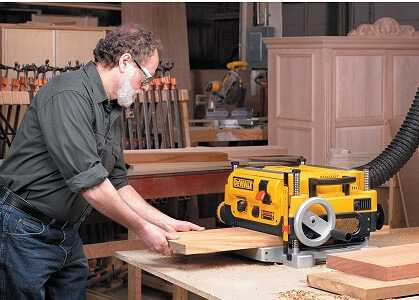 yellow dewalt planer being used by woodworker