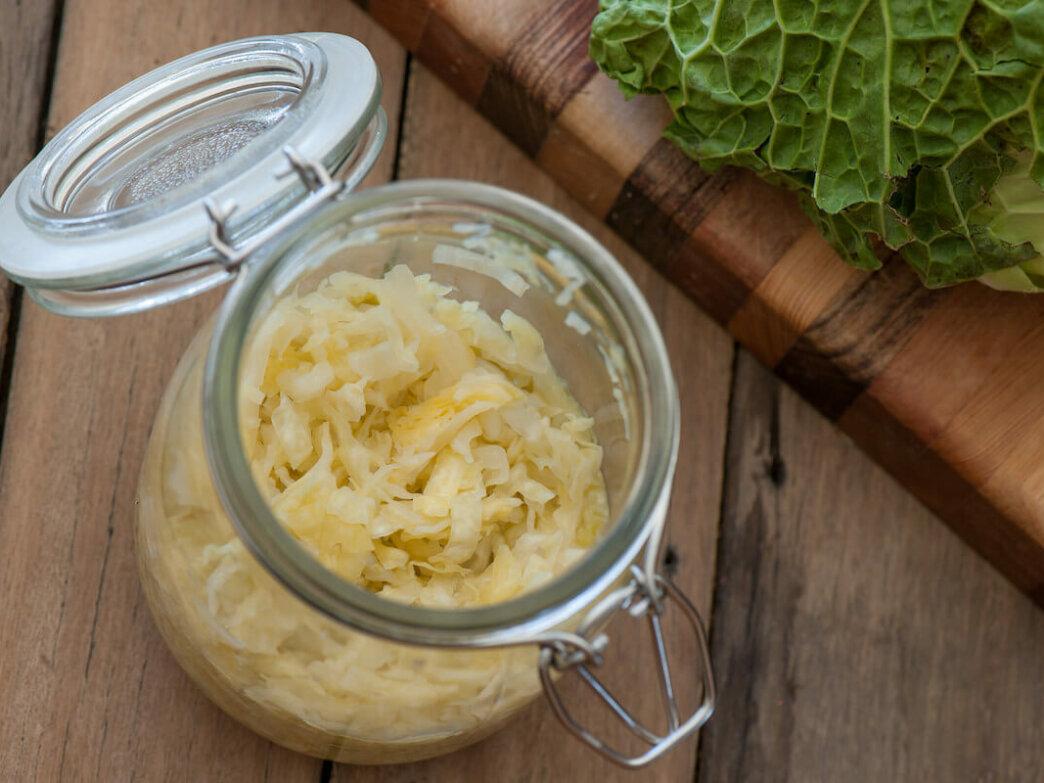 sauerkraut in jar and cutting board on wood table