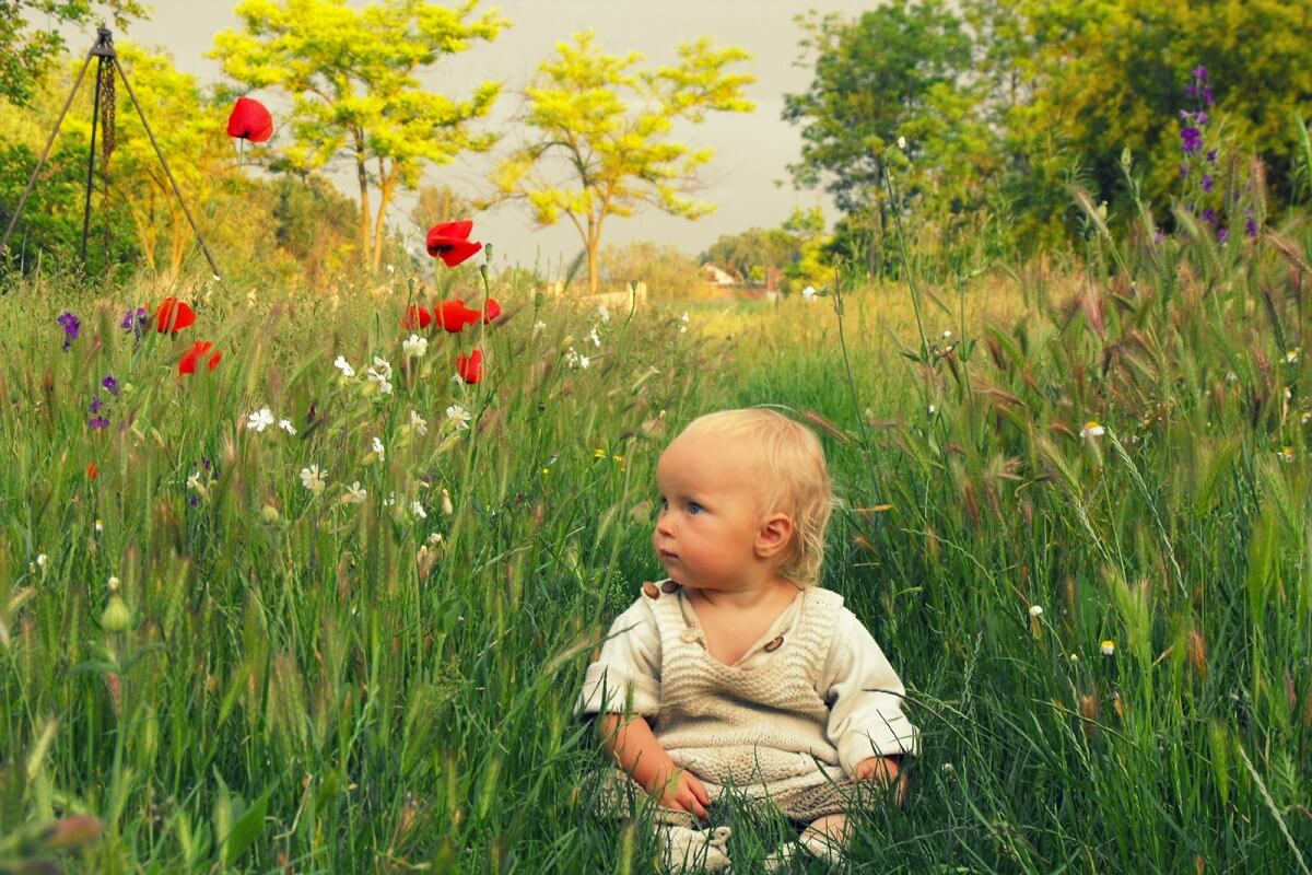 baby sitting in meadow