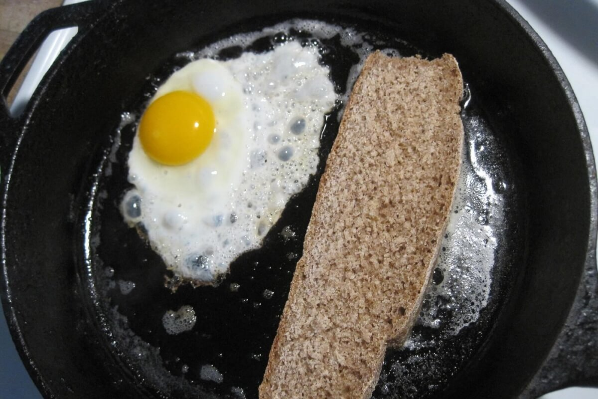 cast iron pan with eggs and bread